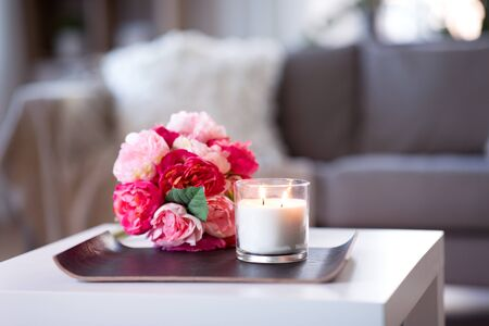 burning fragrance candle and flower bunch at home