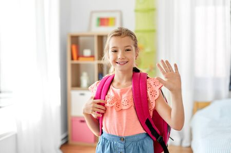 student girl with school bag at home waving hand