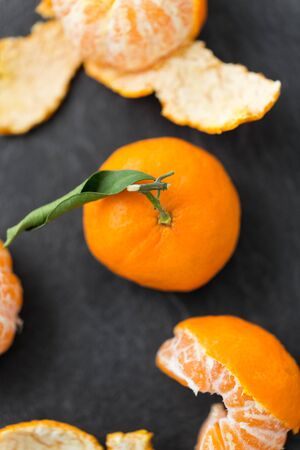 close up of peeled mandarins on slate table top