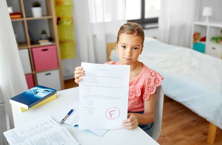 children, education and learning concept - sad student girl with failed school test at home