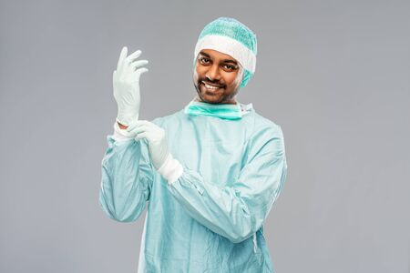 medicine, surgery and people concept - smiling indian male doctor or surgeon in protective wear putting glove on over grey background