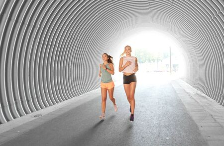 young women or female friends running outdoors Stock Photo