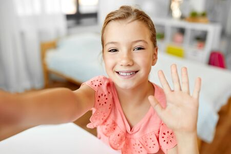 happy girl taking selfie and waving hand at home