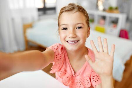 glückliches Mädchen, das Selfie macht und zu Hause mit der Hand winkt