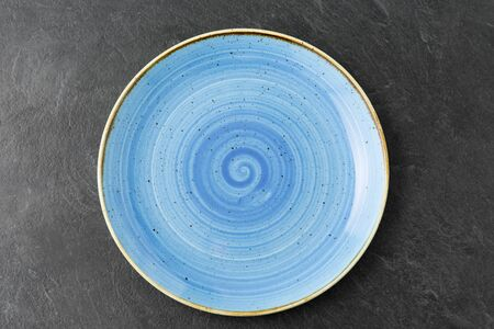 table setting, tableware and eating concept - close up of blue ceramic plate on slate background