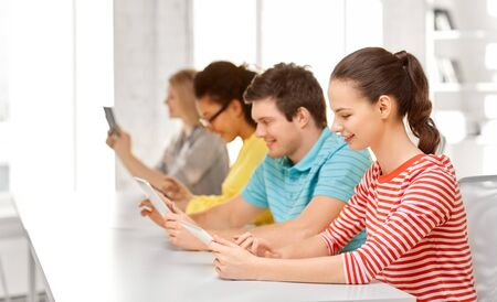 education, technology and learning concept - group of happy international high school students or classmates with tablet pc computers