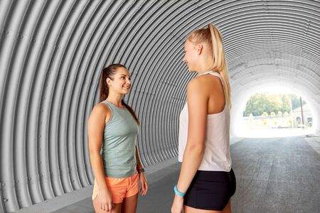 fitness, sport and healthy lifestyle concept - smiling sporty young women or female friends in tunnel