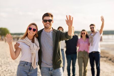 valentines day, relationships and people concept - happy couple with group of friends on beach in summer waving hands Stockfoto