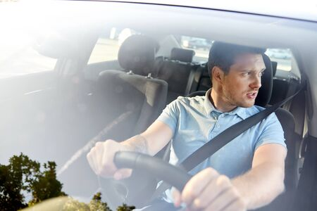 transport, vehicle and people concept - displeased young man or driver driving car in summer