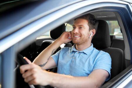 Transport-, Fahrzeug- und Personenkonzept - Mann oder Fahrer mit drahtlosen Kopfhörern oder Freisprecheinrichtung beim Autofahren