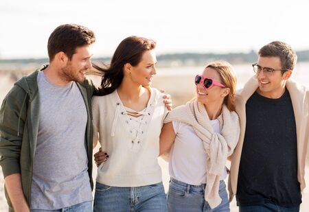 friendship, leisure and people concept - group of happy friends walking along beach in summer