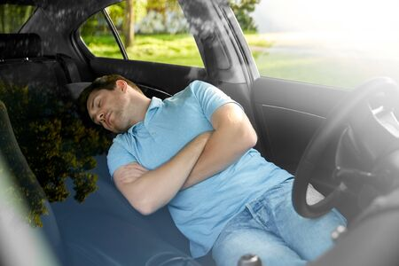 transport, rest and driving concept - tired man or driver sleeping in car