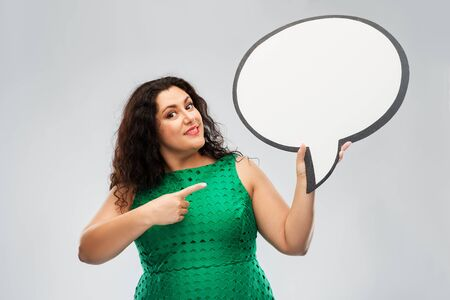people and communication concept - happy woman in green dress holding big blank speech bubble over grey background