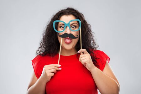 party props, photo booth and people concept - funny woman with big cartoon glasses and mustache showing tongue over grey background