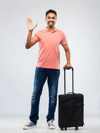 family, tourism and vacation concept - smiling indian man in polo shirt with travel bag waving hand over grey background