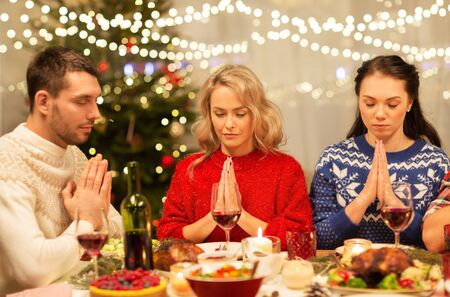 friends praying before christmas dinner at home Stock Photo