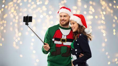 happy couple in christmas sweaters taking selfie