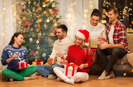 friends celebrating christmas and opening presents Stock Photo - 130804540