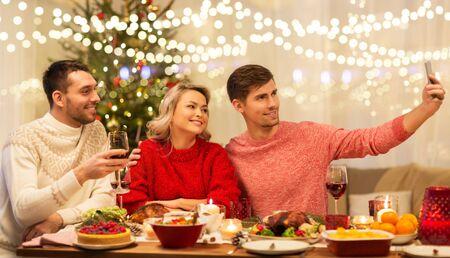 friends taking selfie at christmas dinner