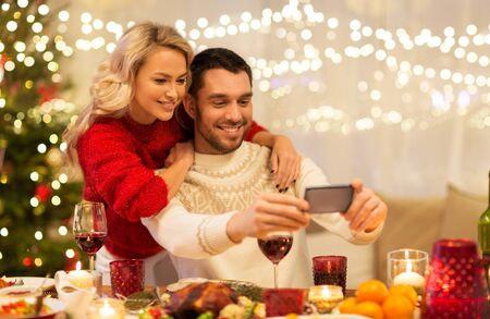 happy couple taking selfie at christmas dinner