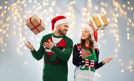 happy couple in ugly sweaters with christmas gifts
