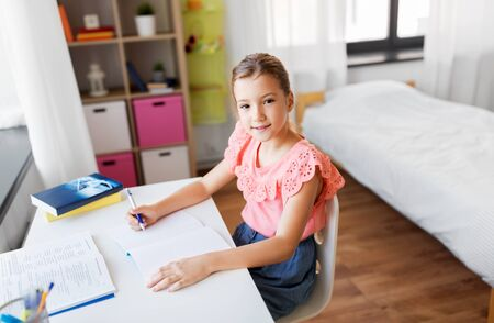 student girl with book writing to notebook at home Stok Fotoğraf