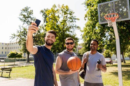 happy men taking selfie at basketball playground