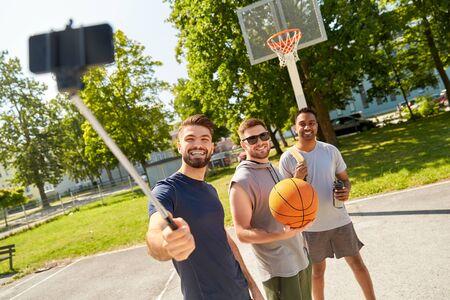 happy men taking selfie on basketball playground