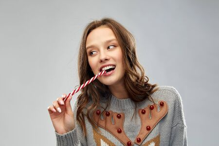 woman in christmas sweater eating candy cane Stockfoto