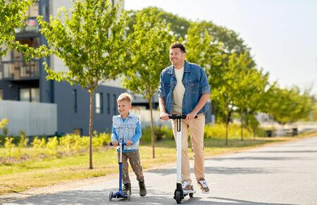father and little son riding scooters in city