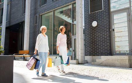 senior women with shopping bags walking in city Фото со стока