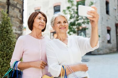 old women with shopping bags taking selfie in city