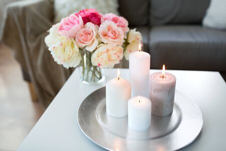 candles burning on table and flowers at cozy home