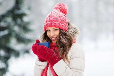 happy young woman with tea cup in winter park