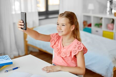 happy girl with smartphone taking selfie at home Stok Fotoğraf