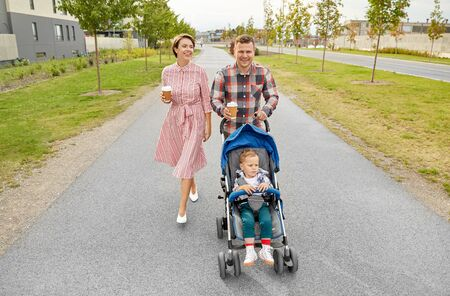 family with baby in stroller and coffee in city Stock Photo