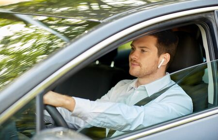 man or driver with wireless earphones driving car