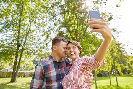 happy couple in park taking selfie by smartphone