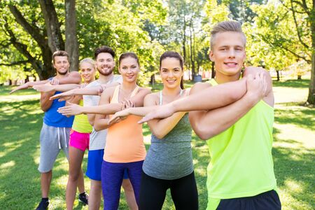 group of happy people exercising at summer park Stok Fotoğraf