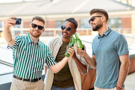men drinking beer and taking selfie by smartphone