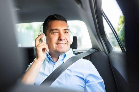 Beifahrer mit Kopfhörern, der im Auto Musik hört Standard-Bild