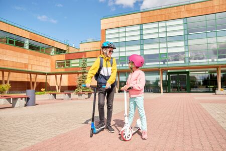 happy school children with backpacks and scooters Stock Photo
