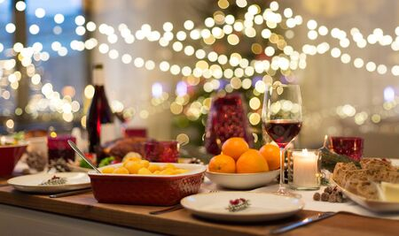 christmas dinner and eating concept - food and drinks on table at home Stock Photo