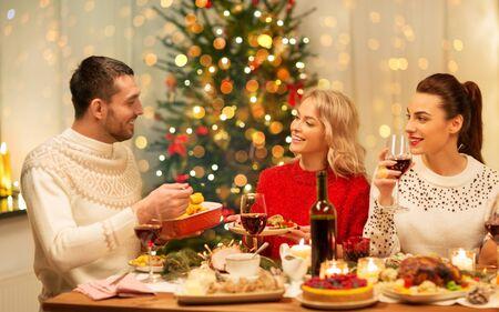 Feiertags- und Feierkonzept - glückliche Freunde, die zu Hause Weihnachtsessen haben, essen und trinken Standard-Bild