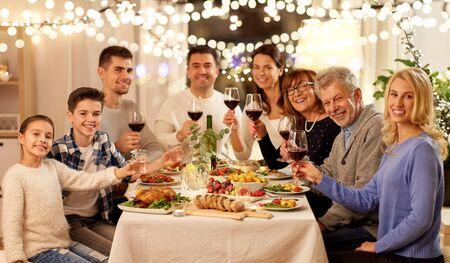 concepto de celebración, vacaciones y personas: familia feliz cenando, bebiendo vino tinto y brindando en casa Foto de archivo