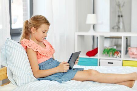 niña sonriente con tablet pc sentada en la cama en casa