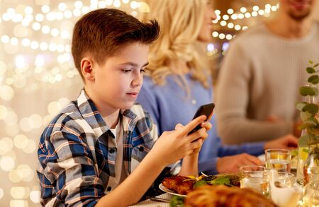 boy with smartphone at family dinner party Stock Photo