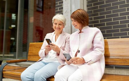 donne anziane felici con smartphone in città Archivio Fotografico