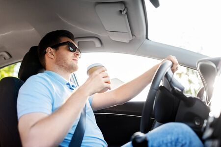 transport, vehicle and people concept - man or driver with takeaway coffee cup driving car Stock Photo
