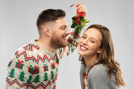 christmas, people and holiday traditions concept - portrait of happy couple in ugly sweaters kissing under the mistletoe over grey background Stockfoto